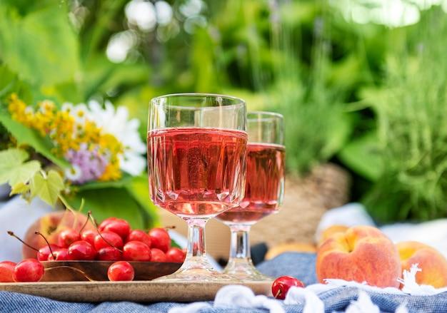 라벤더 밭에서 야외 피크닉. 유리잔에 담긴 장미 와인, 담요에 체리, 밀짚모자