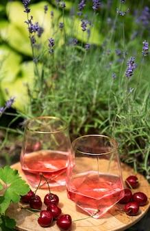ラベンダー畑での屋外ピクニック。ガラスのロゼワイン、木の板のさくらんぼ