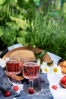 Picnic outdoors in lavender fields.  rose wine in a glass, cherries and straw hat on blanket