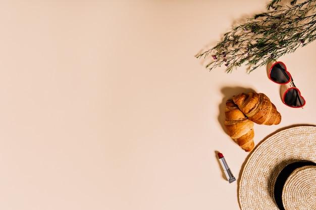 크로와상, 모자, 안경 및 귀여운 작은 꽃의 피크닉 세트가 베이지 색 벽에 놓여 있습니다.