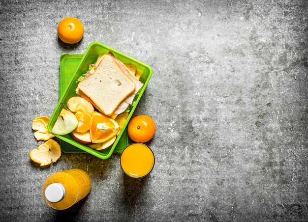 The picnic set sandwiches, orange juice and fruit on the stone table