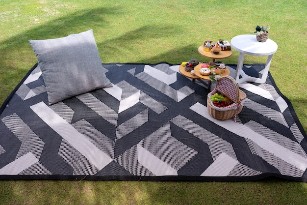 Picnic set with small table with snacks and fruits basket on mat with pillow in garden on green grass field under coconut tree leaf shadow, relax time
