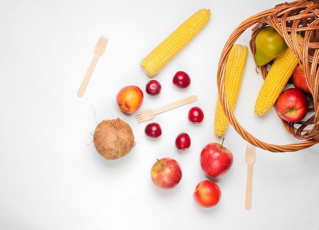 Урегулирование пикника с bassket и фруктами на белой предпосылке.