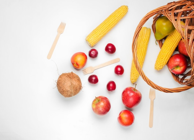 Picnic setting with bassket and fruit on white background.