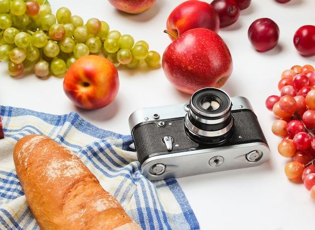 Установка для пикника с камерой, корзиной, фруктами, багетом на белом фоне. джанкет в стиле ретро.