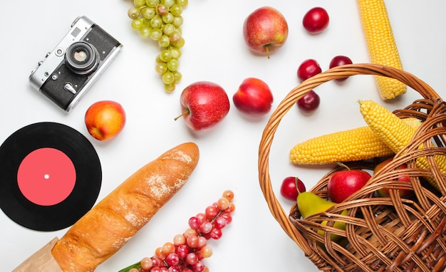 Picnic setting with camera, basket, fruit, baguette on white background. retro style junket.