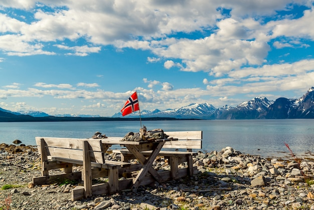 Picnic site rest stop area wooden table decoration and norwegian flag on lake fjord shore.