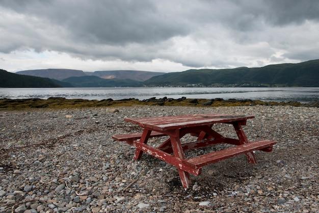 Стол для пикника на галечном пляже, бонн-бей, норрис-пойнт, национальный парк грос-морн, ньюфаундленд а