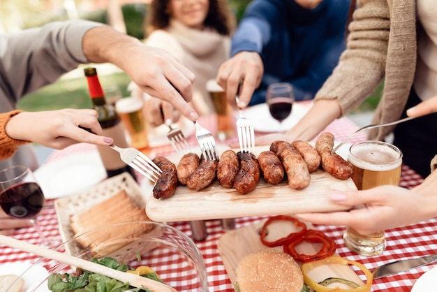 Picnic table with meat vegetables sausages and beer.