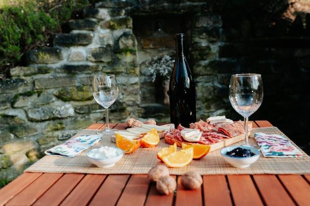 Стол для пикника с сосисками, сыром и традиционными итальянскими блюдами и вином