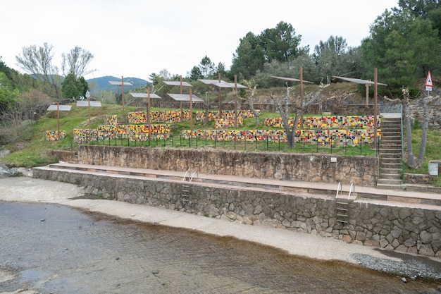 Picnic tables made of pieces of brightly colored ceramic tiles built next to the a natural pool