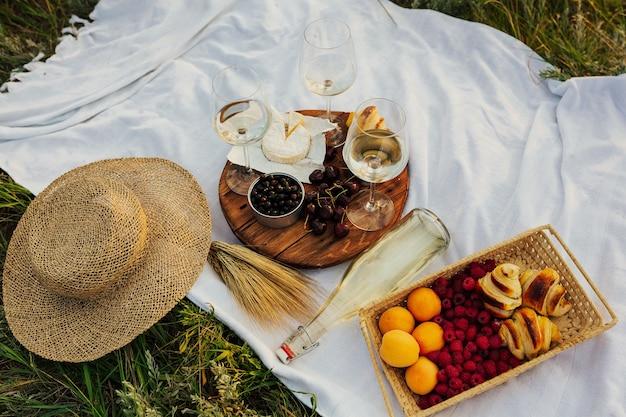 丸い木の板にピクニックタイムのチーズ、ベリー、フルーツ、クロワッサン。