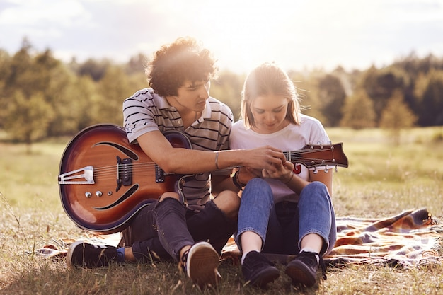 Picnic time. lovely couple in love date on nature, handsome male with curly hair teaches his beautiful girlfriend to play guitar, have good relationship. dating, romance, lifestyle concept