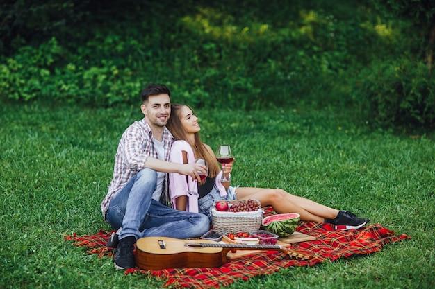 ピクニックタイム。赤ワインと公園で男女。ロマンチックな瞬間。