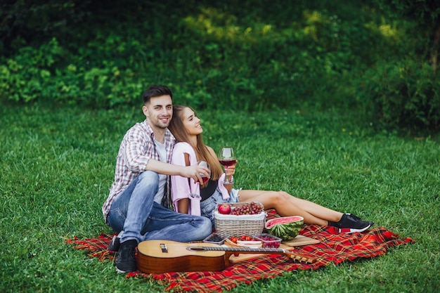 Picnic time. man and woman in park with red wine