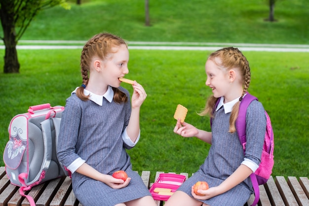 Picnic time. two cute schoolgirls are sitting on a bench, eating breakfast and smiling.