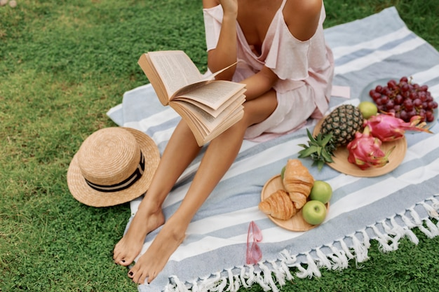 Picnic in tropical garden. romantic asian  woman in pink  dress sitting on cover and reading book