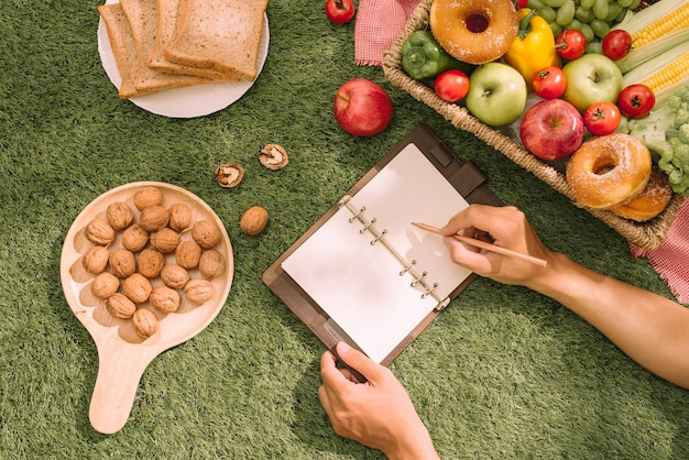 Плетеная корзина для пикника с едой, хлебом, фруктами и апельсиновым соком на красной и белой клетчатой ткани в поле с зеленым фоном природы. концепция пикника.