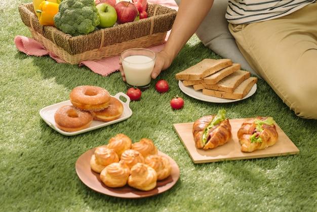 緑の自然の背景を持つフィールドで赤と白のチェックの布に食べ物、パン、フルーツ、オレンジジュースが入ったピクニック籐のバスケット。ピクニックのコンセプト。