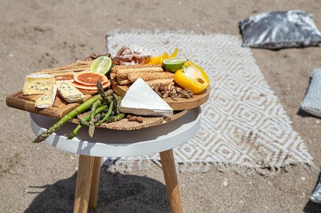 テーブルの上でおいしい美しい食べ物とピクニックをクローズアップ。アウトドアレクリエーションのコンセプト。