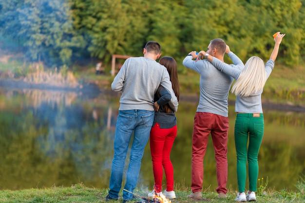 Пикник с друзьями на озере возле костра. друзья компании имея предпосылку природы пикника похода. путешественники отдыхают во время питья. летний пикник. весело провести время с друзьями