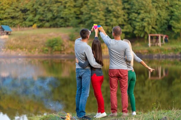 Пикник с друзьями на озере возле костра. друзья, имеющие походный пикник на природе. путешественники отдыхают во время питья. летний пикник. весело провести время с друзьями