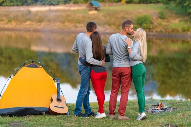 キャンプテントの近くの湖で友人とピクニック。ハイキングピクニック自然背景を持つ会社の友人。飲み物の時間中にリラックスしたハイカー。夏のピクニック。友達と楽しい時間を。