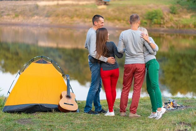 Picnic with friends in at lake near camping tent. company friends having hike picnic