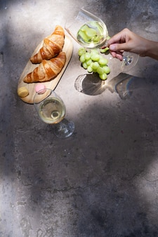 Picnic with white wine and croissants, someone hand holding glass, copy space on the table, shadows overlay