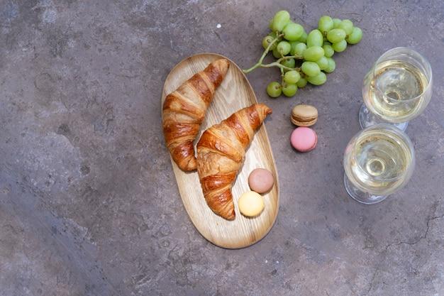 Пикник с вином и круассанами на сером бетонном столе