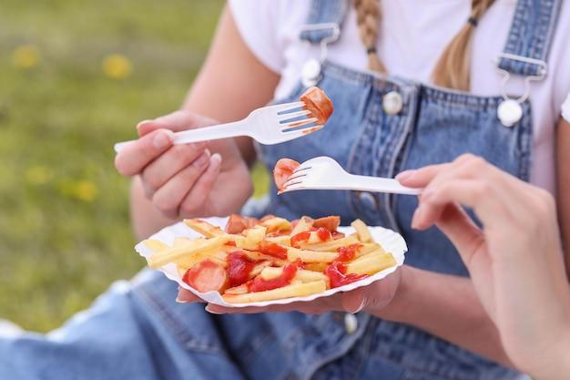ピクニック。女性は屋外の食べ物を食べています