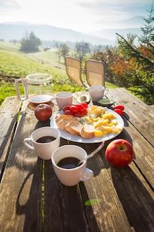 농장에서 피크닉. 산에서 아침입니다. 치즈, 바게트, 토마토, 아보카도, 나무 테이블에 커피