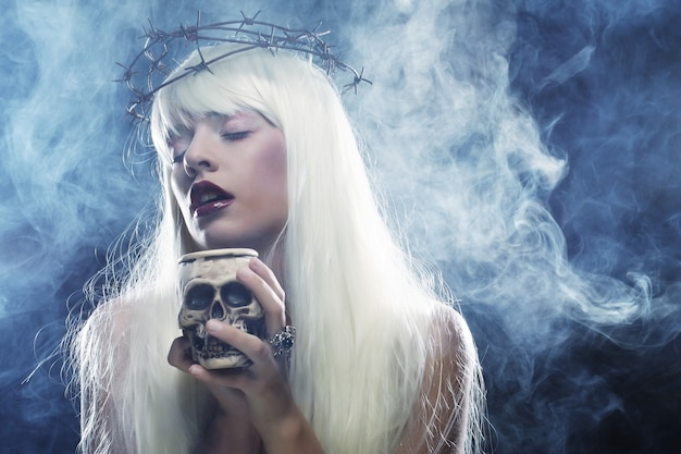 두개골을 가진 아름다운 천사의 긴 머리 여자를 상상하십시오