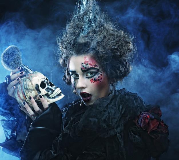 頭蓋骨を持つ美しいファンタジー女性の写真。ハロウィーンのテーマ。