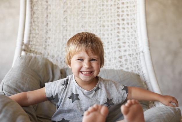 Immagine di adorabile bambina allegra con i piedi nudi e l'acconciatura corta, seduta nella sedia intrecciata a cesto a casa e sorridente ampiamente, sentendosi eccitata e impaziente mentre va a guardare i cartoni animati