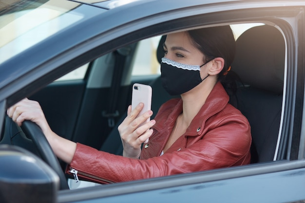 Picture of adorable woman with ponytail holding phone in hands, sanding voice message or setting route black protective mask driving automobile.