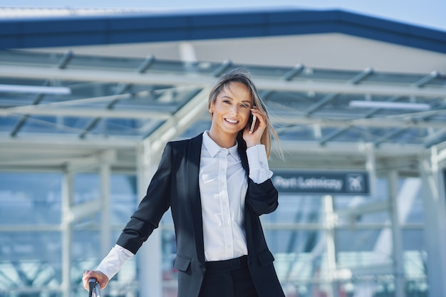 Picture of adult female passenger using smartphone at the airport