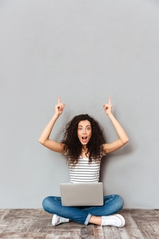 Picture of agitated woman sitting in lotus pose on the floor suddenly remember important information putting index fingers in the air over grey wall