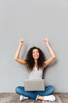 Picture of agitated woman sitting with legs crossed on the floor being happy and excited putting index fingers in the air over grey wall