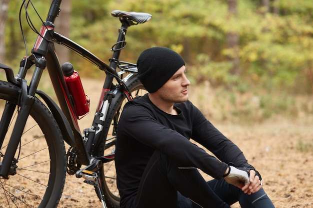 Picture of amateur sportsman, sitting on ground, keeping his arms together, being thoughtful, having greens, being near his bicycle, leading healthy lifestyle.