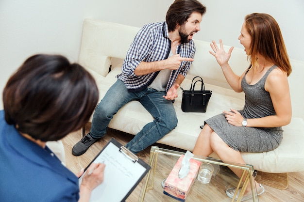 A picture of angry couple screaming and yelling to each other. both of them are unhappy and not pleased. they are waving with their hands. therapist is writing down. she is looking at piece of paper.