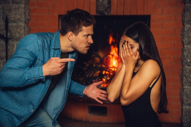 Picture of angry and mad young man stand in front of woman and point on her. she covers face with hands. they sit at fireplace.