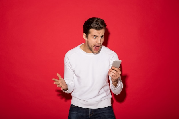 Picture of angry man in sweater screaming at smartphone over red wall