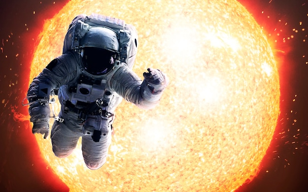 Picture of astronaut spacewalking in front of the sun. elements of this image furnished by nasa