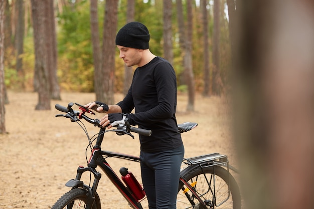 Picture of attentive adventurous man standing in middle of forest, holding his bicycle, looking at smartphone screen, looking for way back, using gps, choosing shortest way.