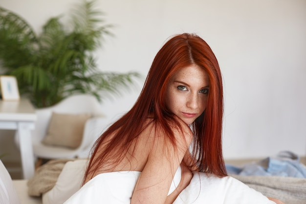 Picture of attractive 21 year old caucasian female model with shiny red hair and natural make up sitting on bed, covering body with white blanket, staring with mysterious expression