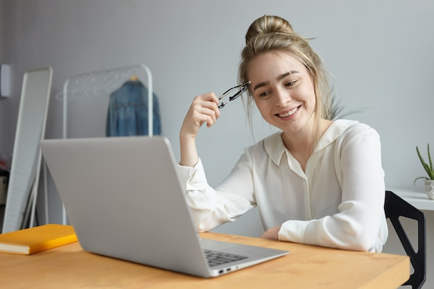 Picture of attractive cheerful student girl with hair knot surfing internet on generic portable computer, sitting at table at home, smile broadly, watching blog, communicating with friends online