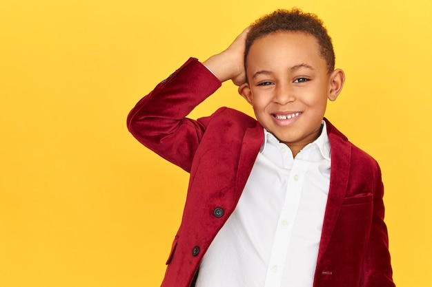 Picture of attractive fashionable african little boy looking at camera with broad cheerful smile, feeling uncomfortable, scratching back of head, forgot about your birthday, posing at copy space wall