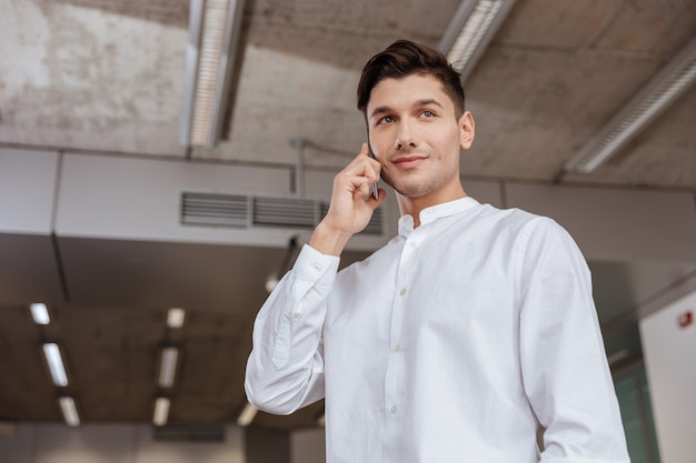 Picture of attractive man dressed in white shirt talking by the phone indoors. coworking. looking aside.