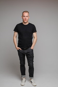 Picture of attractive man wearing a black t-shirt and jeans stands with hands in pockets isolated on grey wall